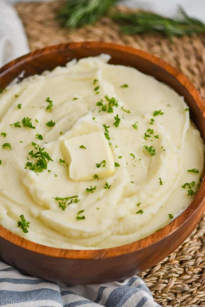 instant pot mashed potatoes in a wooden bowl with parsley garnish and a square of butter on top