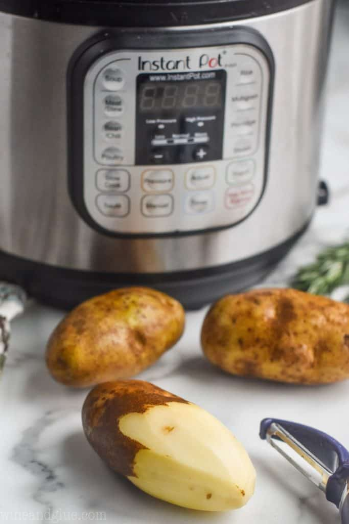 three russet potatoes for creamy mashed potatoes, one half peeled, sitting in front of an instant pot
