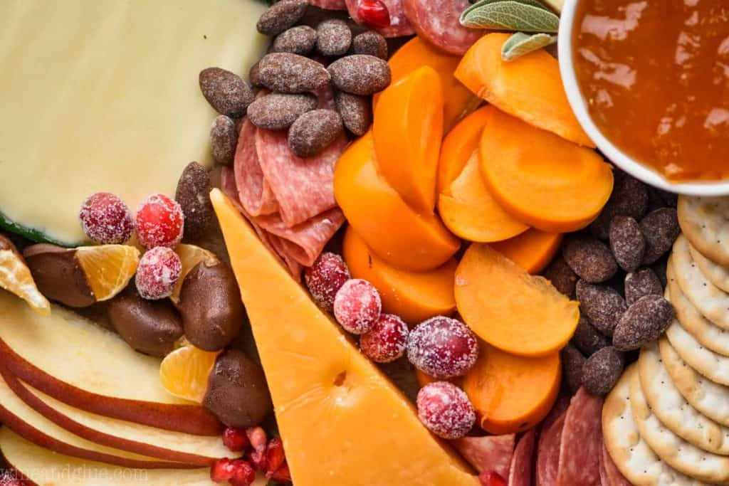A close up photo of sliced persimmons, sliced apples, sliced meats, crackers, clementine slices dipped in chocolate, and candied nuts.