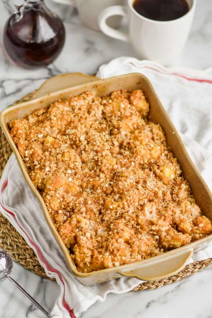 overhead view of baked French toast casserole in a brown ceramic baking dish on a cloth napkin and straw circle placemat with bottle of syrup