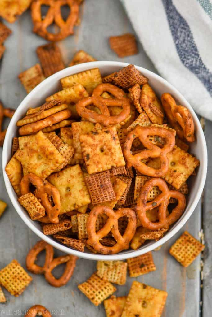 overhead of a white bowl full of chex mix recipe with crackers, cereal, and pretzels
