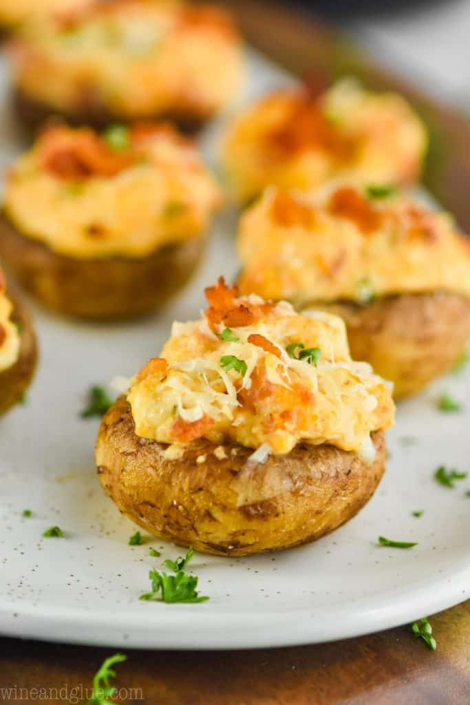 picture of stuffed mushrooms with cream cheese, fresh parsley, and fresh parmesan, with more in the background
