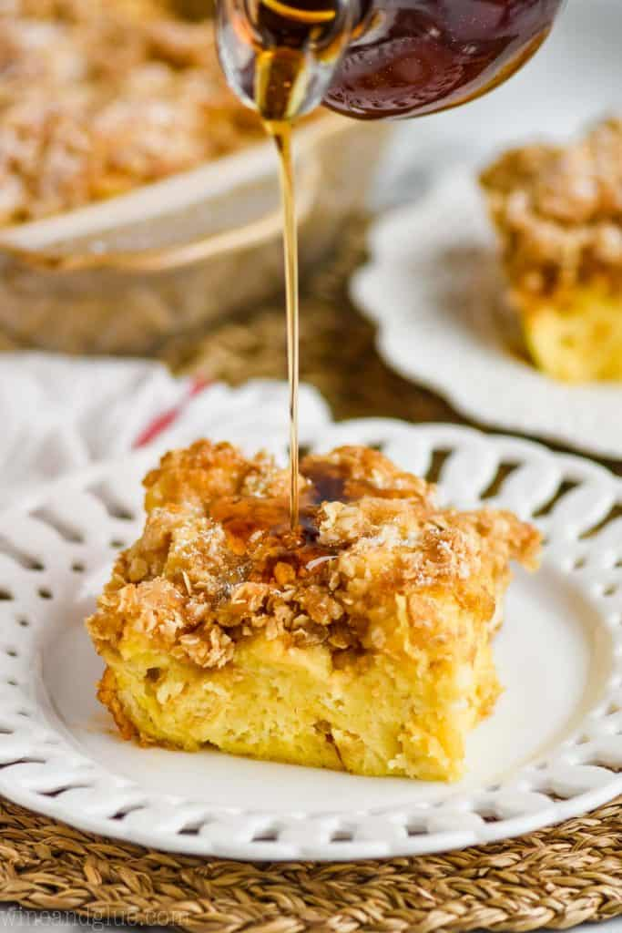 a square piece of French toast casserole on a fancy whit plate with streusel on top, and syrup being poured on