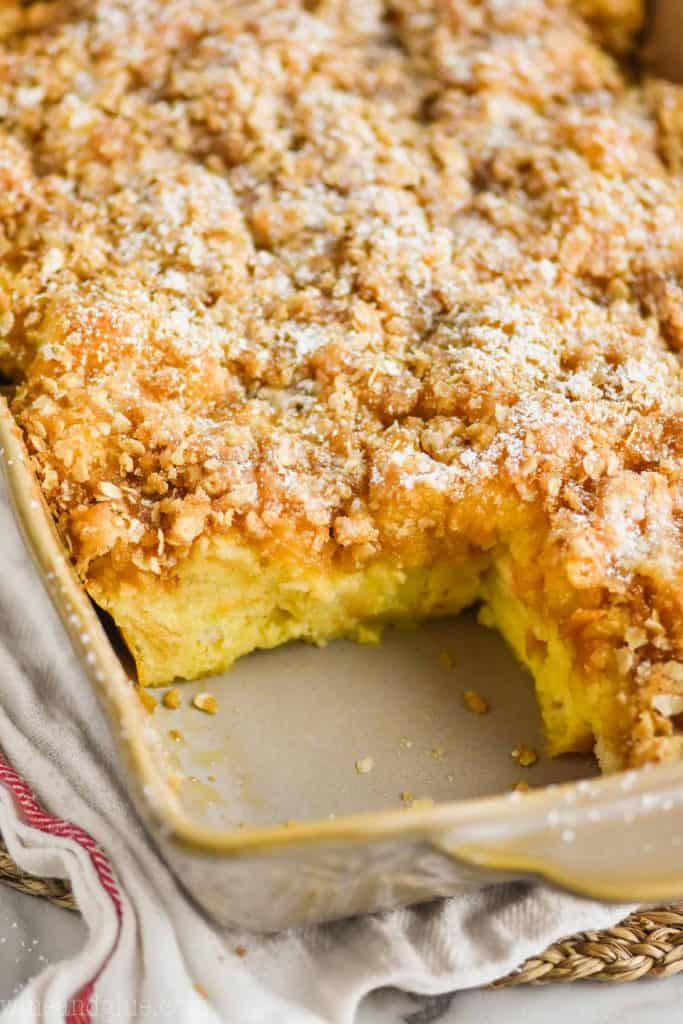 close up of a French toast casserole recipe that is still in the baking dish with one piece missing, it is topped with a crispy streusel topping and powdered sugar