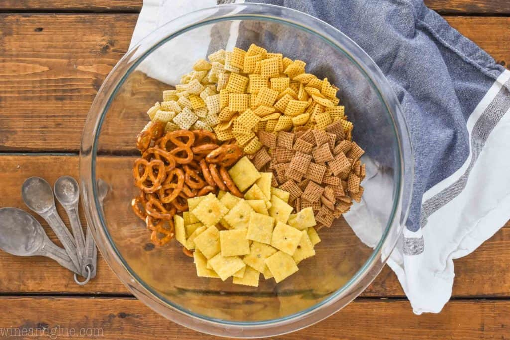 overhead view of a clear mixing bowl with dry ingredients for chex mix
