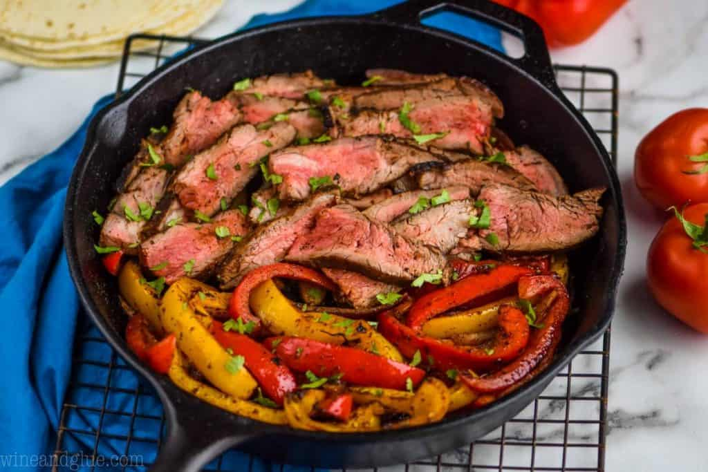 landscape side view of a cast iron skillet with cooked steak and peppers for steak fajitas