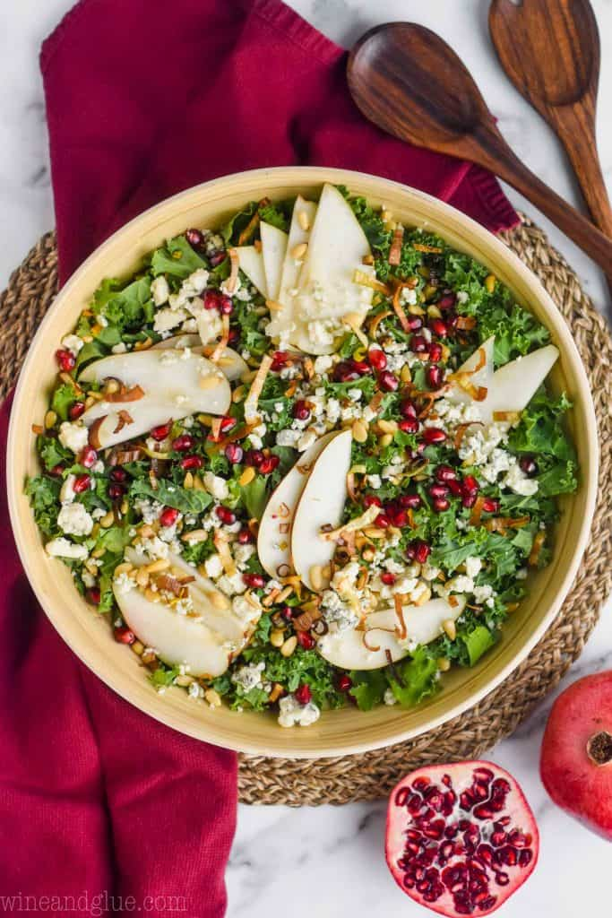 overhead view of a wooden serving bowl full of winter salad recipe with sliced pears, kale, blue cheese, crispy leeks, and pine nuts on a maroon cloth napkin with a pomegranate cut in half and a whole pomegranate next to it