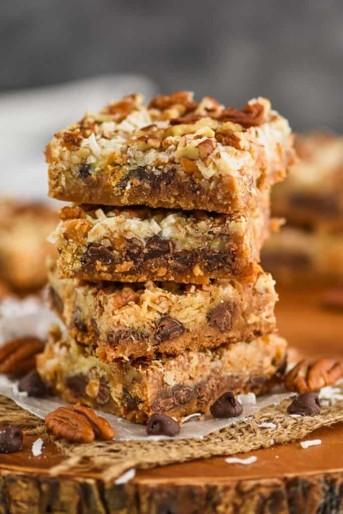 a stack of four magic cookie bars, layer of graham cracker, chocolate chip, coconut, and pecan pieces visible