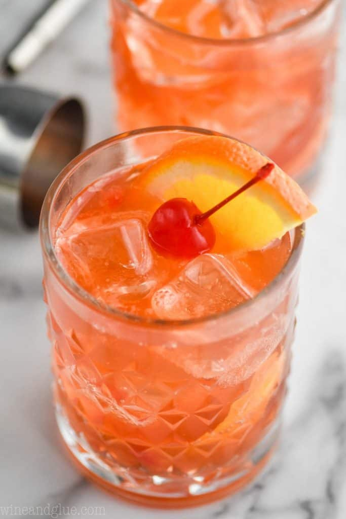 up close view of an old fashioned drink recipe with a ice cubes, a maraschino cherry, and an orange wedge