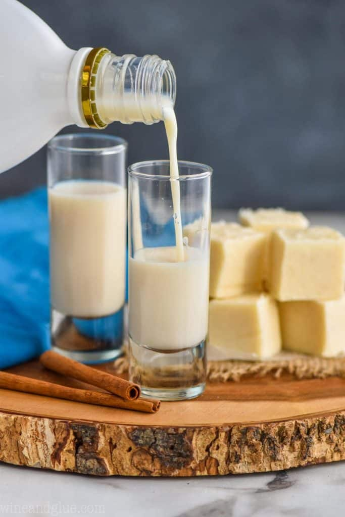 two tall shot glasses on a wood board with fudge next to them and rum Chata being poured into one
