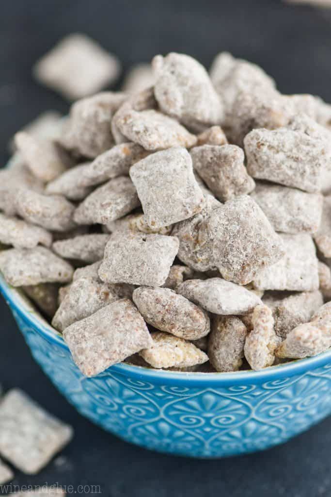 a blue detailed bowl against a dark surface overflowing with a puppy chow recipe