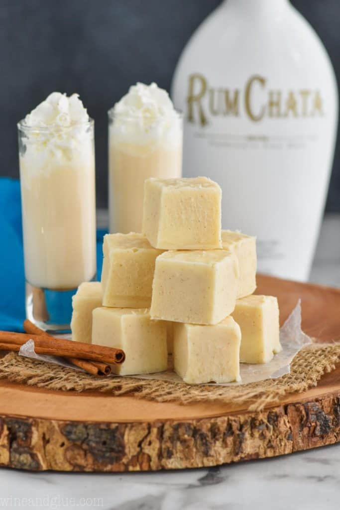 a pile of white rum Chata fudge on a wood board, with cinnamon sticks next to it, two tall shot glasses full of rum Chata in the background and a bottle of rum Chata in the distance
