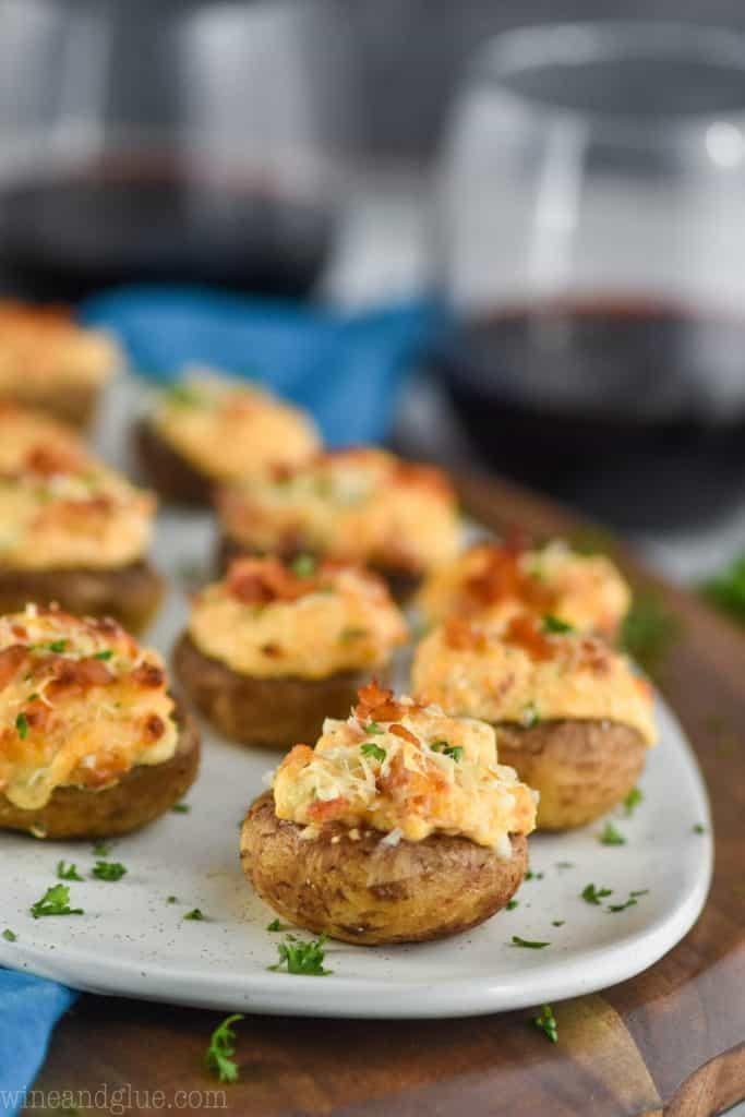 a white plate with stuffed mushroom recipe on it that is garnished with fresh parsley and red wine in the background