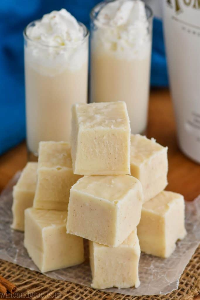 a pile of white chocolate fudge with two shot glasses full of rum Chata in the background topped with whipped cream