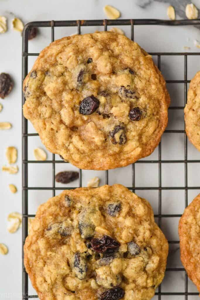 close up overhead view of a chewy oatmeal raisin cookie on a wire cooling rack