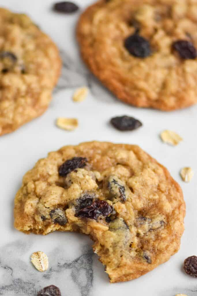close up of an oatmeal raisin cookie on a marble surface with a bite missing