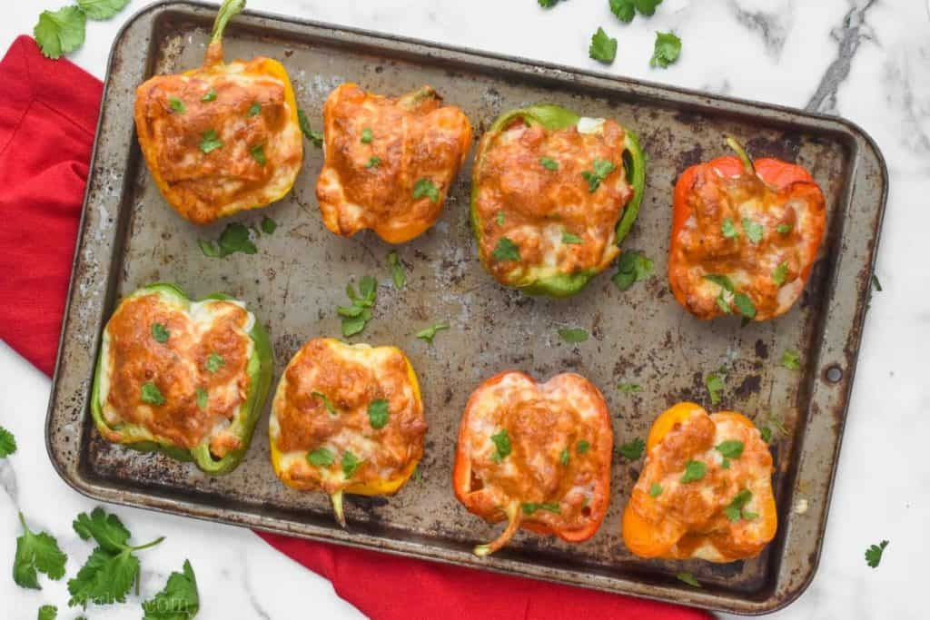 overhead view of 8 bell pepper halves that are chicken stuffed peppers, topped with brown melted cheese on an old tray and garnished with cilantro