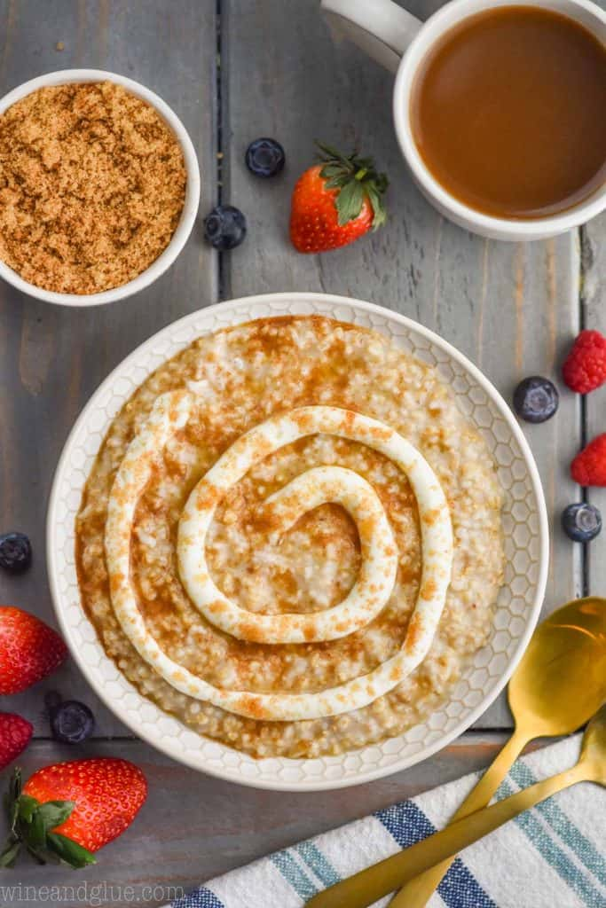 overhead view of cinnamon roll steel cut oats that have a swirl of frosting and brown sugar on top, lots of berries surrounding the bowl