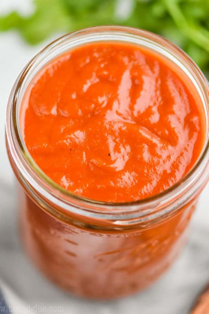 close up overhead of thick and creamy red enchilada sauce in a mason jar