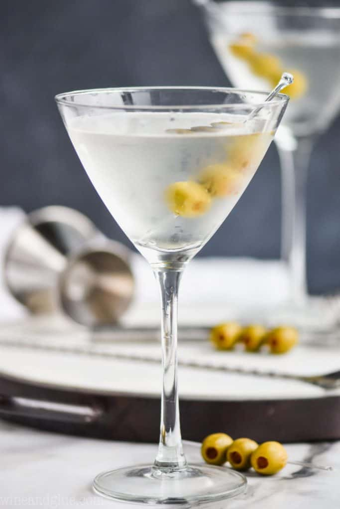 a frosted martini glass that has been chilled full of a gin martini recipe with three olives on a toothpick, a metal jigger and another gin martini on a tray in the background
