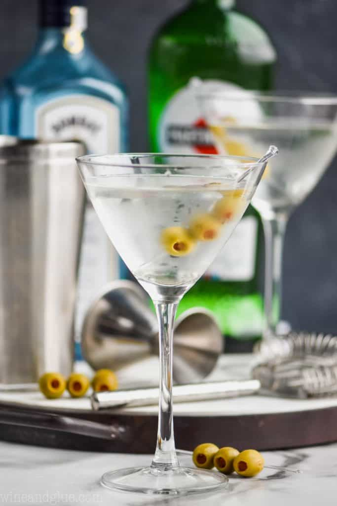a gin martini in a frosted martini glass with a tray full of bar tools, a bottle of Bombay saphhire, and a bottle of dry vermouth in the background