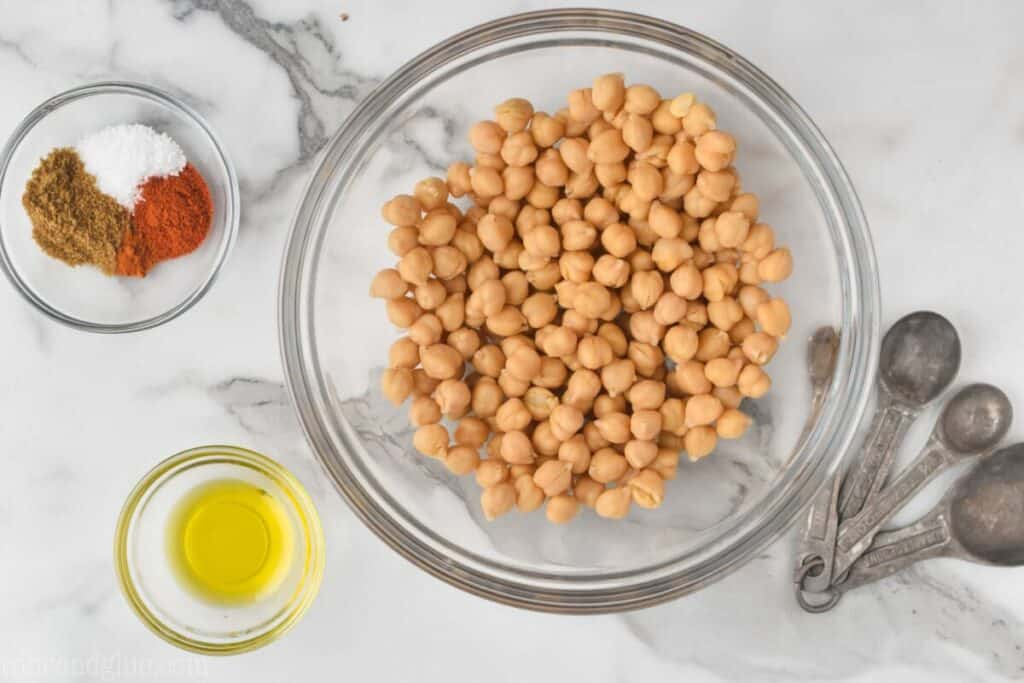 overhead view of drained and rinsed chickpeas in a bowl next to oil and spices