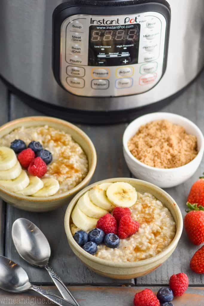 two small bowls of instant pot steel cut oats recipe garnished with berries and banana slices next to a small bowl of brown sugar with an instant pot in the background