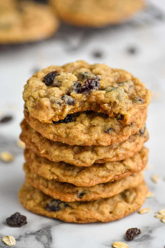 stack of oatmeal raisin cookies on a marble countertop with more on a cooling rack in the background