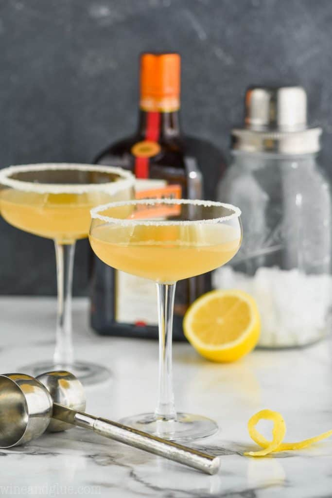 two coupe glasses rimmed with sugar holding a sidecar recipe with a double sided metal jigger in the foreground, a lemon twist off to the side and a bottle of cointreau and a cocktail shaker in the background