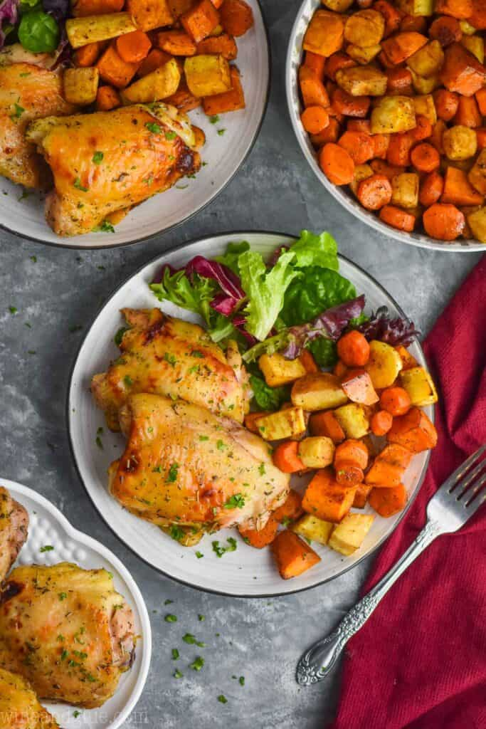 overhead view of chicken thighs on a plate with roasted root vegetables and salad
