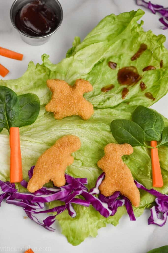 a piece of iceberg lettuce serves as the background for a dinosaur scene made out of veggies and dinosaur chicken nuggets