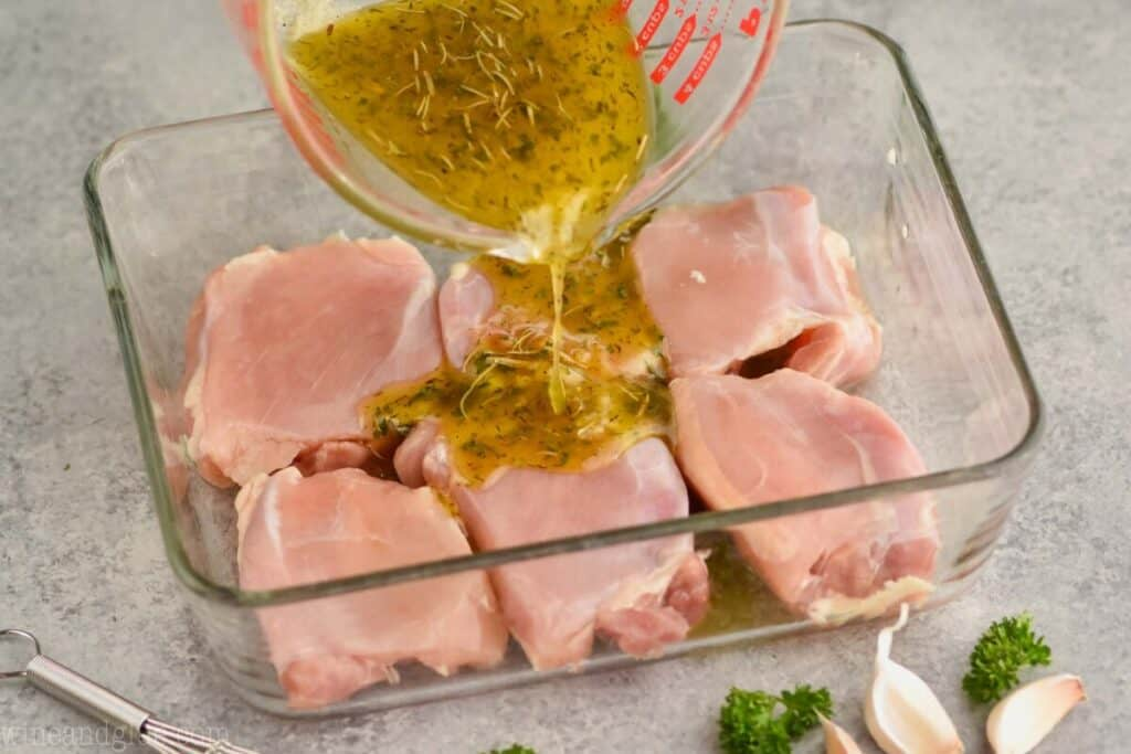 a marinade being poured over skinless chicken thighs in a baking dish