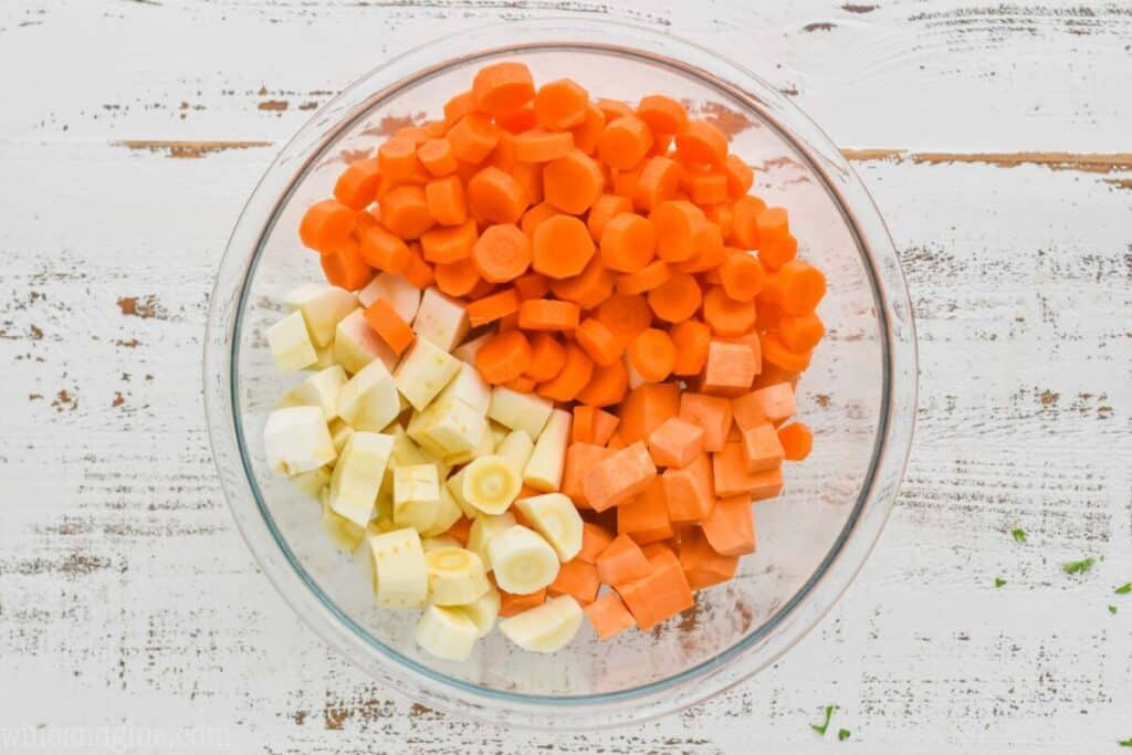 overhead view of a bowl full of raw cut up parsnips, carrots, and sweet potatoes