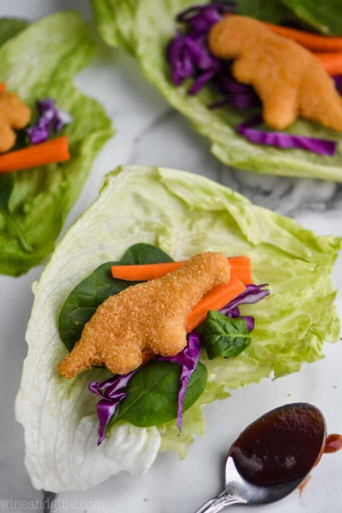 a lettuce wrap for kids made with dinosaur chicken nuggets, cabbage, spinach leaves, and carrot pieces all on a piece of iceberg lettuce