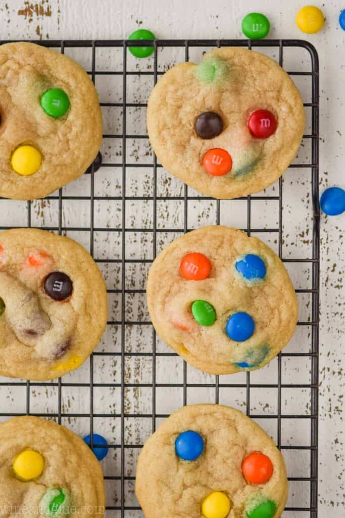 overhead photo of six m and m cookies on a wire cooling wrack on a white wood board with m & ms around them
