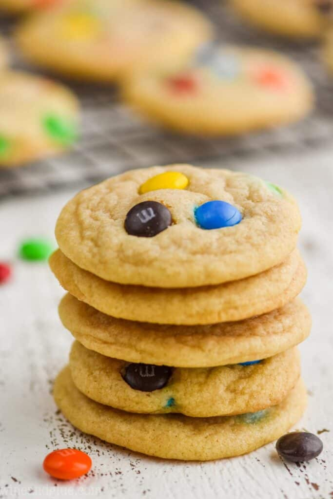 stack of five m n m cookies with more on a cooling rack in the background