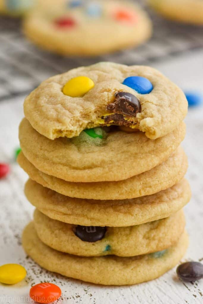 A stack of 6 m&m cookies. The first one in the stack has a small bite out of it.