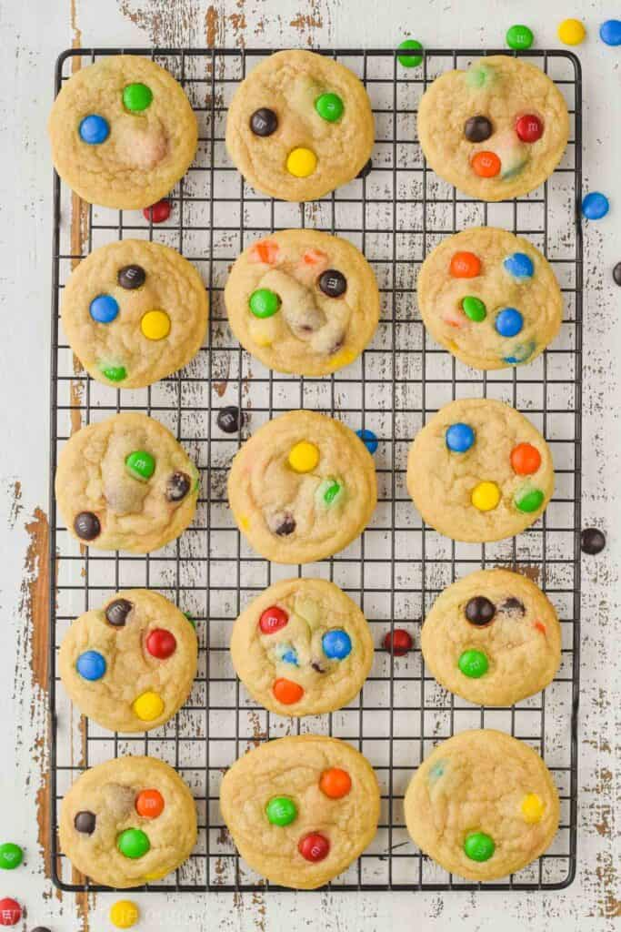 way pulled back overhead photo of a batch of m&m cookies on a wire cooling rack