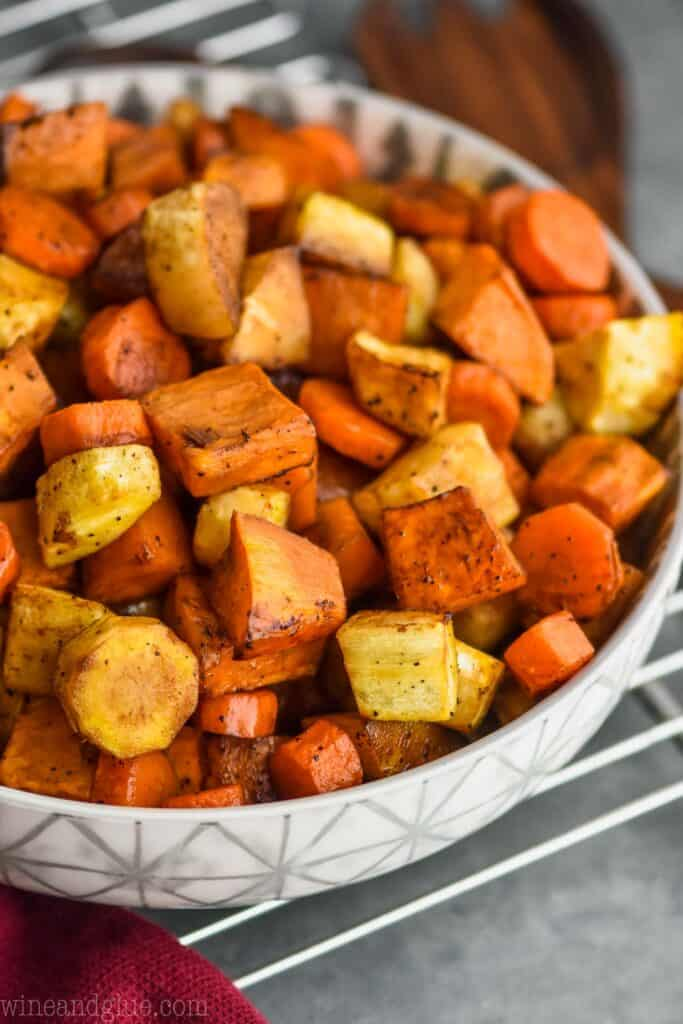 side view of a serving bowl full of oven roasted root vegetables