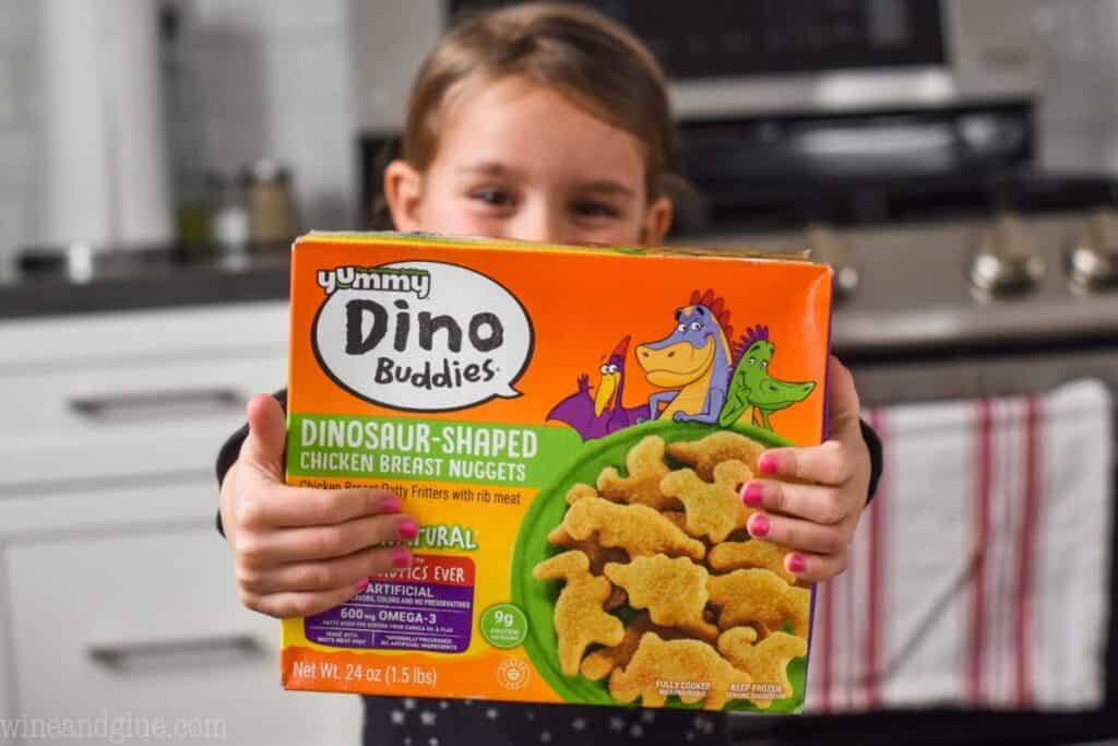 little girl holding a box of yummy Dino buddies
