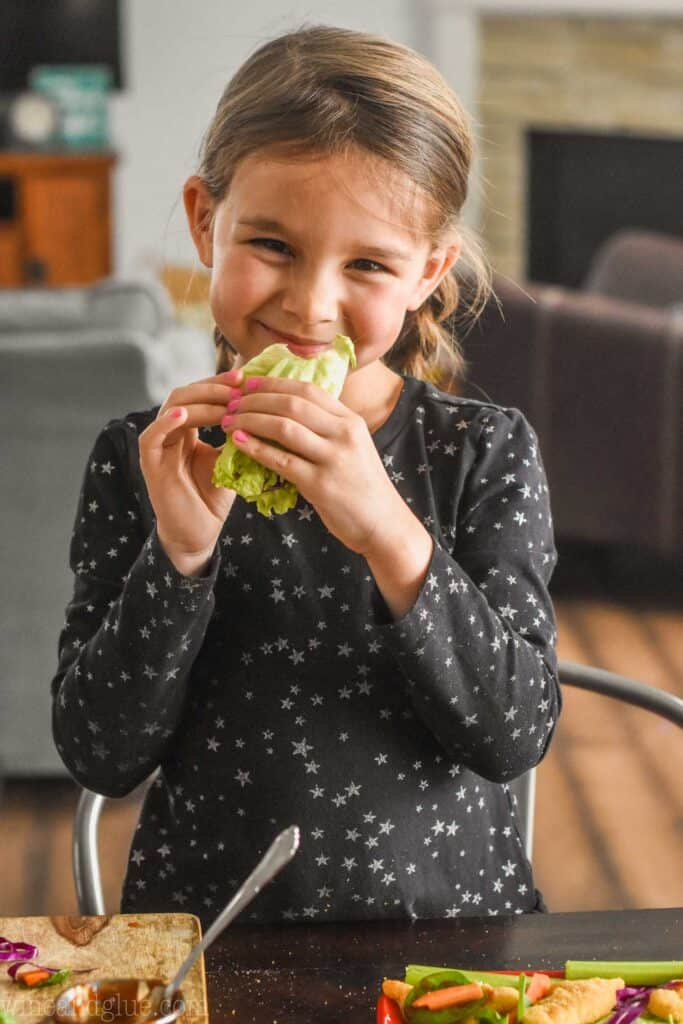 a little girl in a black dress eating a lettuce wrap for kids