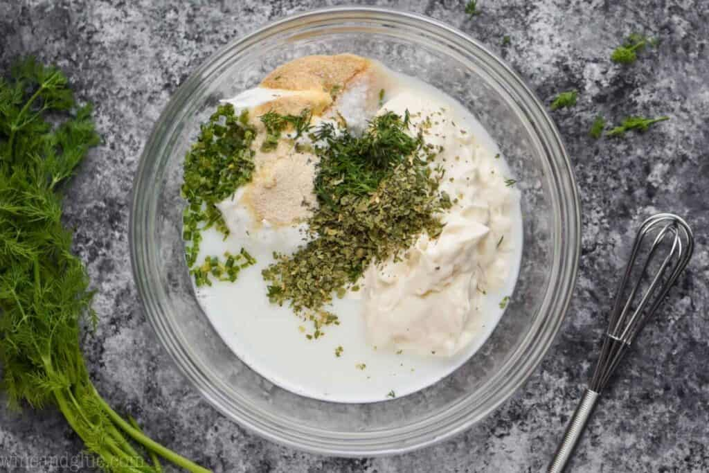 overhead of a bowl of ranch dressing ingredients with fresh dill next to it and a small whisk