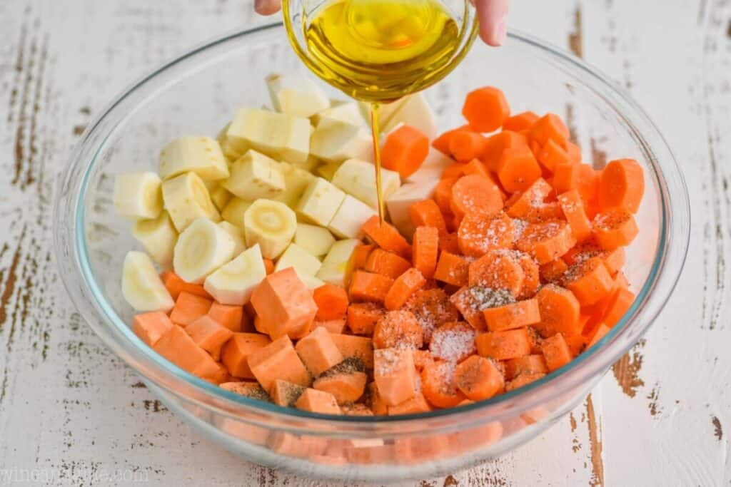 pouring olive oil into a large bowl full of raw cut up parsnips, sweet potatoes, and carrots