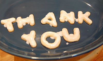 "A plate of frosted sugar cookies in letters that spell out ""THANK YOU"""
