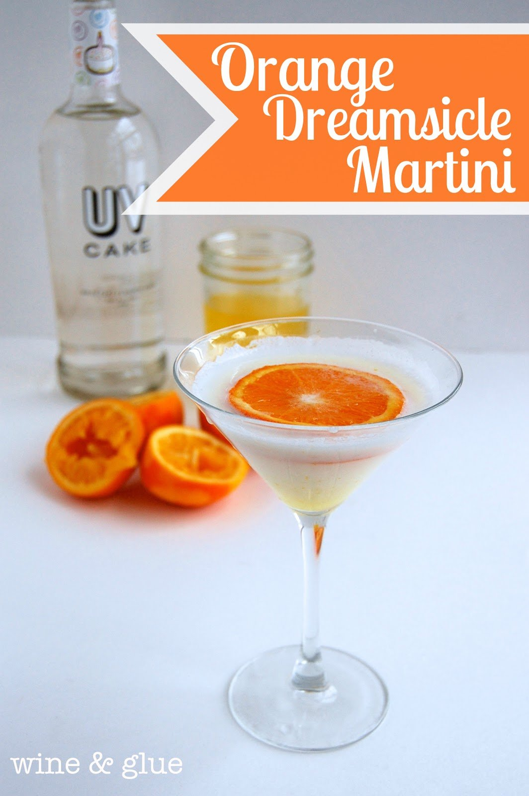 A glass of Orange Dreamsicle Martini that is an opaque white color with a circular slice of an orange.