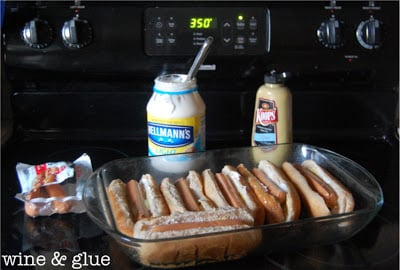 In a glass oven pan, there are six vegetarian hot dogs in buns. In condiment jars, there is mayo and mustard.
