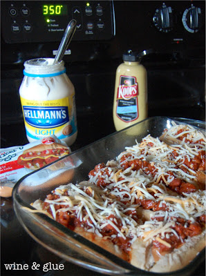 In an glass oven pan, there are several vegetarian hot dogs topped with vegetarian chili and shredded vegan cheese.