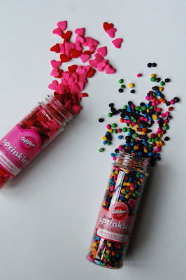 Two containers of sprinkles. One holding red and pink hearts, and the other holding multicolored circles