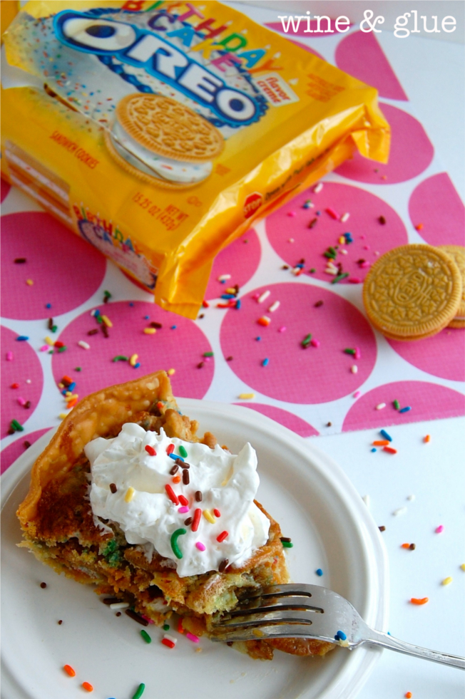 A slice of Oreo Cookie Birthday Cake Pie that is topped with a dollop of whip cream and rainbow sprinkles. In the background is a package of yellow Birthday Cake Oreos