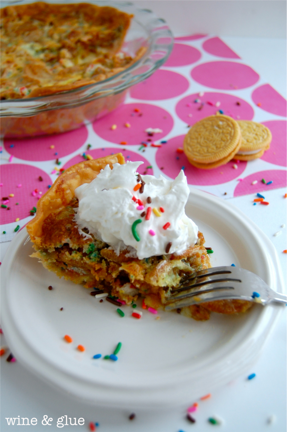 A slice of Oreo Cookie Birthday Cake Pie that is topped with a dollop of whip cream and rainbow sprinkles